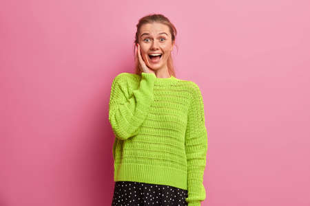 Amused happy European girl laughs out loudly, feels excited and very glad, keeps hand on cheek, stands upbeat, dressed in oversized knitted sweater, poses against rosy background, yells wow. Stock Photo