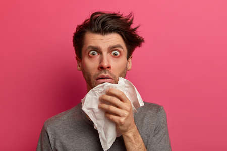 Stunned sick man has flu, virus or allergy respiratory, red watery eyes, blows nose in tissue, finds out about serious disease, poses over pink background. Health, medicine and symptoms concept 스톡 콘텐츠