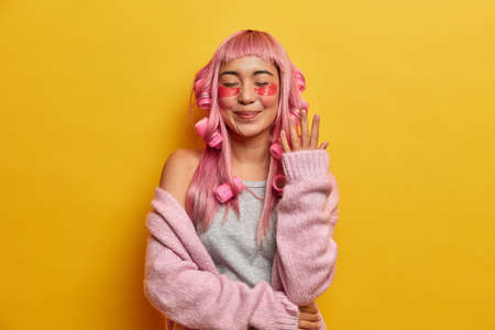 Satisified smiling woman with pink hair, applies rollers and beauty pads, dressed in rosy sweater, enjoys spare time for spending on herself, stands with eyes closed and hand raised, models indoor 版權商用圖片
