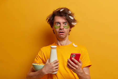 Shocked emotional man has cereals for breakfast, leads healthy lifestyle and has proper nutrition, types message on smart phone impressed to get stunning news has messy hair undergoes beauty treatment