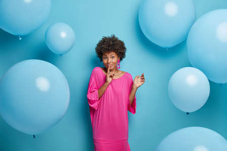 Happy mysterious dark skinned Afro American woman makes silence gesture, asks to be quiet, dressed in pink long dress, spreads rumors, poses against blue background with inflated balloons around.