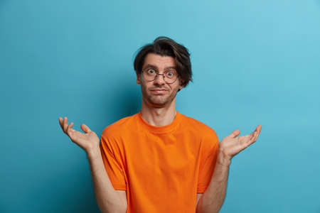 Clueless adult man says dont know, maybe, who cares, looks disinterested in question, has doubts, stands bewildered, spreads palms sideways, wears optical glasses and orange t shirt, isolated on blue
