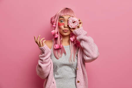 Funny pink haired Asian woman has rollers on head, covers eye with tasty sweet doughnut, wears collagen patches to reduce wrinkles, undergoes beauty treatments, isolated over rosy background. 版權商用圖片