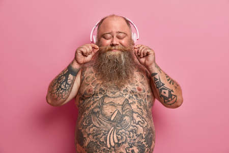 Isolated shot of overweight bearded man curls mustache, closes eyes, listens favorite songs in headphones, found music station or funny podcast, has tattooed belly, models against rosy wall