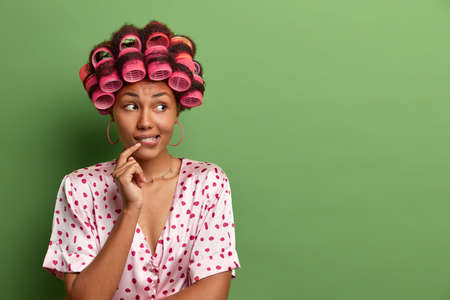 Thoughtful housewife bites lips and thinks how to look brilliant on coming party, wears hair rollers for curly hair, dressed in nightwear, poses against green background, blank empty space aside