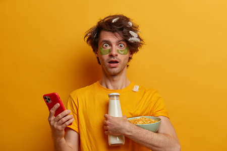 Shocked male model reacts surprisingly on receieved message, uses mobile phone, going to have breakfast, holds bowl of cereals and milk, applies collagen patches under eyes, has much things to do