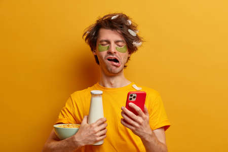 Tired male student studied all night before exam, has lack of sleep, yawns with drowsy expression, texts message on smartphone, holds bottle of milk and cornflakes, going to have breakfast in morning