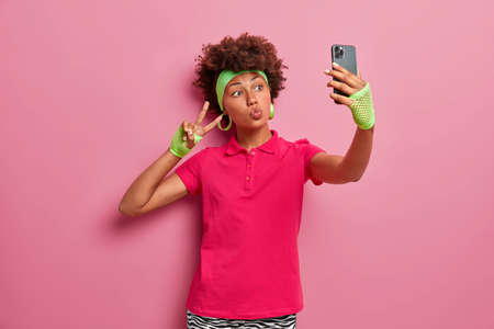 Curly haired active woman in pink t shirt, headband and sport gloves, takes selfie, makes victory gesture, holds mobile phone, being obsessed with social networks poses indoor, rosy studio wall