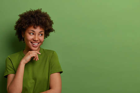 Kind optimistic young Afro American woman looks aside, keeps hand gently under chin, imagines awesome event, wears casual green t shirt, poses indoor, blank space right for your advertisement
