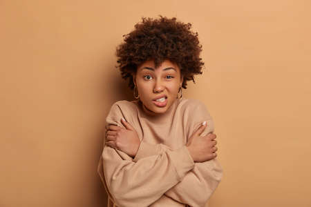 Displeased dark skinned woman hugs herself, feels freezed during cold day, winter is coming, clenches teeth, shakes during chilling weather, stands indoor. Fearful female afraids of something