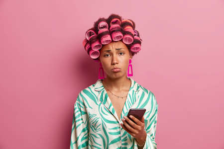 Displeased housewife sad boyfriend doesnt call, holds mobile phone and waits for desirable message, upset because of postponed date, wears hair curlers and silk gown, looks unhappily at camera Stockfoto
