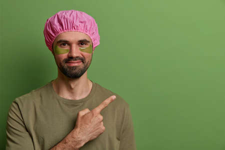 Horizontal view of satisfied unshaven man wears pink bath hat, casual t shirt, has eye skin treatment, applies collagen pads for reducing fine lines, points at blank space, advertises some product 版權商用圖片