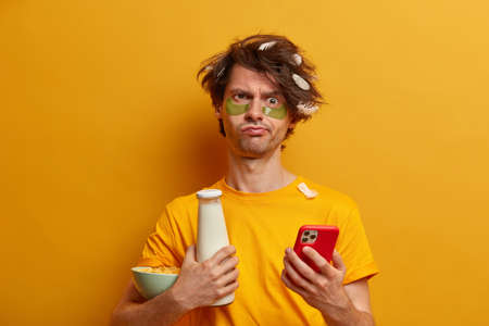 Healthy breakfast for feeling energy whole day. Gloomy displeased man with messy hairstyle smirks face waits for important call holds cellular bottle of milk, cornflakes has drowsy look after sleeping