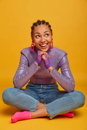 Pleased dreamy young Afro American woman concentrated above, holds hands under chin, sits in lotus pose against yellow background, dressed in stylish clothes and sport gloves, smiles broadly