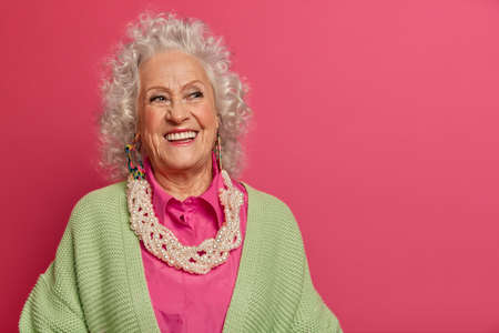 Portrait of thoughtful grey haired lady recalls pleasant memories, smiles happily, wears stylish outfit, cares about skin, uses anti aging cosmetics, models against pink background, copy space