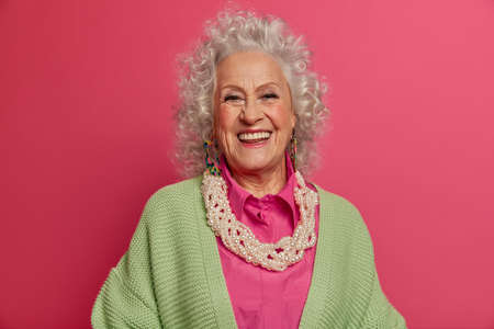 Headshot of good looking elderly woman smiles broadly, makes photo for long memory, being in happy mood, dressed in elegant clothes, isolated on pink background. Beauty, style, age, fashion concept Stock Photo