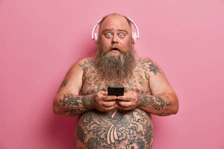 Surprised plump man stares at camera and says wow, texts with friend via smartphone, wears headphones on ears, listens music, poses shirtless, has tattooed body. Technology and leisure concept