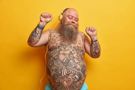 Happy bare man with fat stomach, tattooed belly, enjoys listening new song in headphones, raises arms, clenches fists, moves with rthythm, feels carefree, enjoys fantastic bits, poses indoor Banque d'images