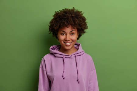 Half length shot of lovely young Afro American woman with curly natural hair, smiles happily and looks at camera with joy, wears purple sweatshirt, receives good news, isolated on green background 版權商用圖片