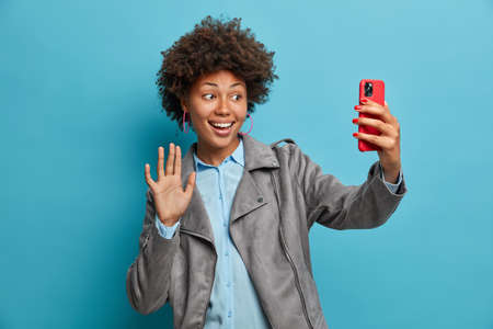 Charming positive dark skinned friendly woman enjoys informal meeting online, waves palm and says hi in smartphone, uses video messanger, takes selfie, wears stylish grey jacket, greets friend