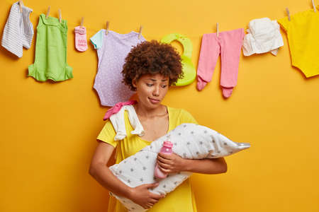 Newborn child sleeping on mothers hands. Puzzled woman holds baby wrapped in towel, bottle with milk, takes care of infant, cannot understand why daughter crying, busy doing chores about house