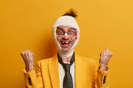 Positive optimistic funny guy becomes victim of street crime, clenches fists, has missing teeth after being beaten, wrapped in bandage, isolated on yellow background. People and injuries concept