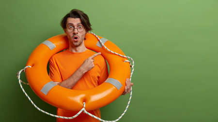 Emotional stunned man poses with safety equipment, uses lifebuoy on rescue, points at copy space, has shocked expression, isolated over green background. Time for swimming. Accident prevention