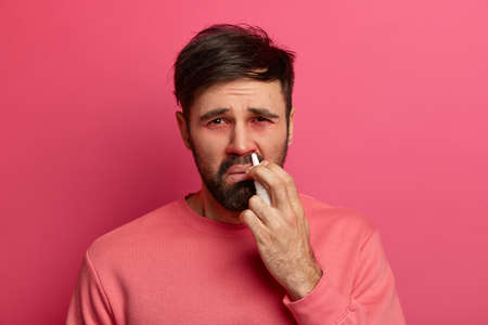 Upset ill man sprays medicine for allergy in nose, caught cold, suffers from rhinitis, has red swollen eyes, dressed in casual wear, poses against pink background. Disease treatment concept. 스톡 콘텐츠