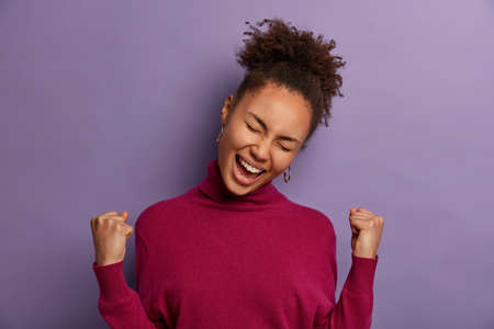 Successful euphoric African American woman celebrates amazing news, lucky to win lot of money, triumphs as dream come true, tilts head, dressed in casual turtleneck, isolated on purple background