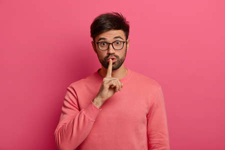 Shush, please. Wondered surprised man demands silence, prohibits speaking, keeps index finger pressed to lips, looks surprisingly through spectacles, asks not spread rumors, isolated on pink wall