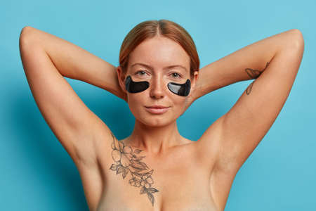 Serious European woman has well cared body with tattoo, healthy skin, stands naked indoor, applies collagen patches under eyes, undergoes beauty treatments, isolated on blue background. Cosmetology 版權商用圖片