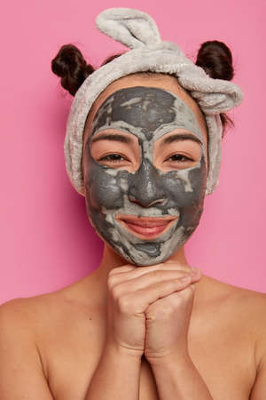 Close up portrait of pleased Asian woman applies clay mask, cleans skin from black dots, keeps hands under chin, wears headband, stands with bare shoulders against pink background. Spa and wellness 版權商用圖片
