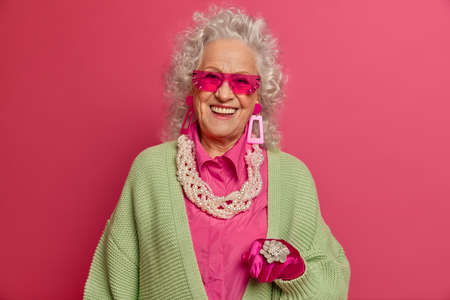 Good looking senior woman with curly grey hair, white perfect teeth, wears pink sunglasses and jewelry, stylish clothes, poses indoor. Fashionable grandmother on pension cares about herself.