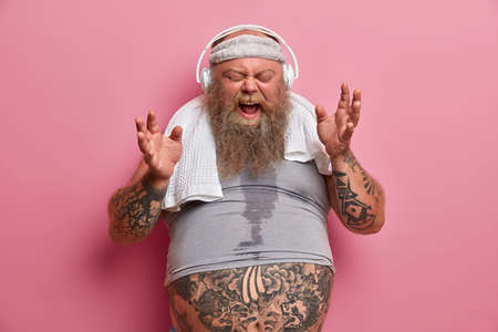 Emotive chubby hipster listens music in headphones, sings song loudly, dressed in sports wear, has fitness training to loose weight, poses against rosy background. Athlete thick bearded man indoor Stock Photo