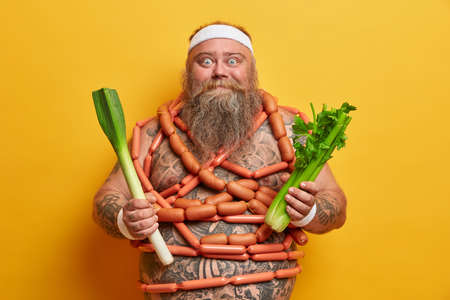 Positive overweight man with thick belly and sausages around, obsessed with food, keeps to diet, holds green leek and celery, poses against yellow background. Weight loss and healthy lifestyle concept