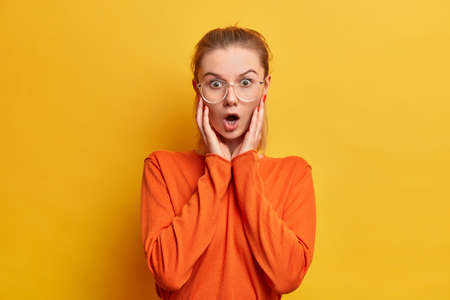 No words to describe my shock. Embarrassed stupefied European girl with stupefied expression, keeps mouth widely opened, sees awful things, wears orange jumper, big glasses, yellow background