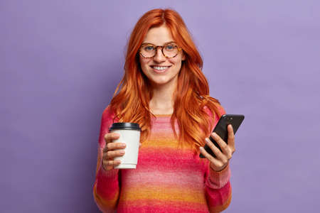 Horizontal shot of positive redhead woman smiles pleasantly, holds mobile phone and take away coffee. Positive lady in casual clothes enjoys online communication, poses against purple background Banque d'images