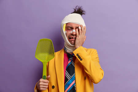 Depressed man cries after fight and assault, covers injured face with hand, has dark shiner and missing teeth, suffers from abuse and violence, holds kitchenware, dresses bright suit and colorful tie Stok Fotoğraf
