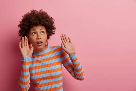 Scared African America woman afraids of something keeps palms raised, tries to protect herself from thing falling from above, keeps mouth opened, concentrated upwards, isolated on pink background