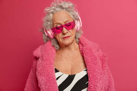 Portrait of serious thoughtful elderly woman wears massive headphones, listens melancholic music, enjoys lyrics song, wears trendy sunglasses and warm coat, concentrated down with pensive expression