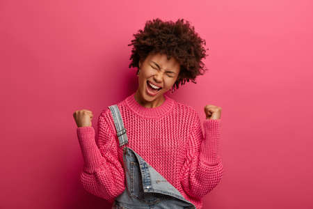 Relieved satisfied Afro American woman triumphs over success and victory, makes champion dance, fist bump, happy to achieve goal, tilts head and exclaims with joy, dressed in fashionable clothes Foto de archivo