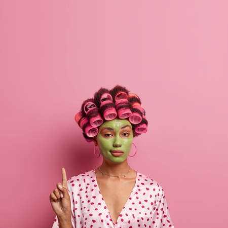 Confident ethnic woman with hair rollers, green facial mask, looks mysteriously at camera, points above, shows copy space for your advertisement, pink background. Beauty, cosmetology concept