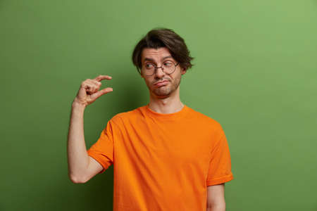 Unimpressed adult European man shows little bit gesture, dissatisfied with amount of something, asks some more, wears orange t shirt, poses against green studio wall. Please give me few more Stock fotó