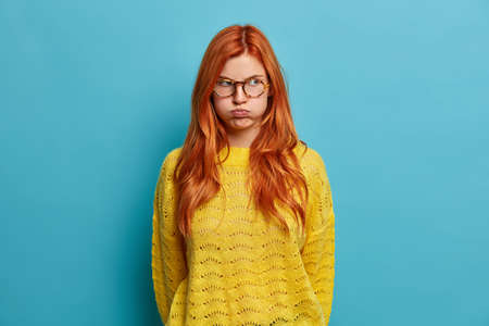 Discontent redhead European woman pretends to be offended blows cheeks and looks with unhappy grimace. Angry irritated ginger girl in yellow sweater poses against blue background. Bad mood concept