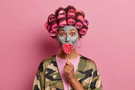 Beauty woman with hair curlers, gets ready for special event, wants to look fresh and young, applies mud mask for rejuvenation, covers mouth with lollipop, has fun, looks surprisingly at camera