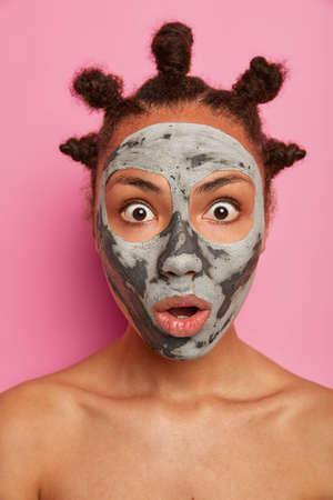 Emotional shocked Afro American woman wears mask for face, reduces wrinkles on complexion, stands naked, has well cared healthy skin, reacts on something surprising, isolated over pink background