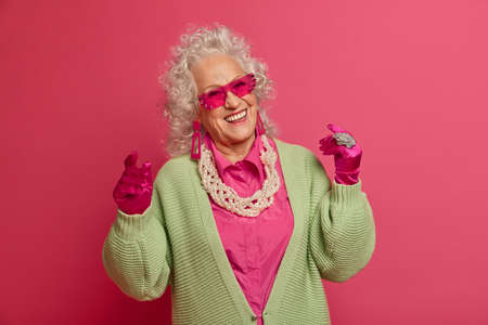 Carefree beautiful grandmother has fun and dances, moves with rthythm of music, remembers her youth, wears elegant outfit, gloves and sunglasses, forgets about problems, isolated on pink background