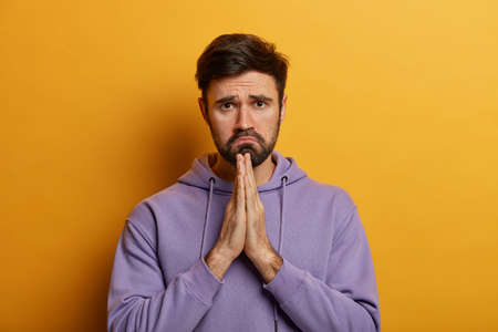 Whining gloomy man with sad expression presses palm in pray, says please, begs for favour, badly needs help, asks for apologize, wears purpe hoodie, poses against yellow studio wall. Help me