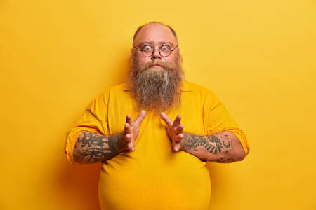 Waist up shot of surprised plump man has big belly, stares with bugged eyes, raises hands, afraids of something, dressed in casual t shirt, isolated on yellow background. Overweight surprised guy