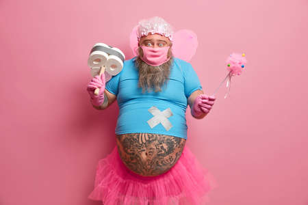 Overweight bearded father does household duties, poses with toilet paper, dreams fairy will do all work, holds magic wand, wears mask, isolated on pink background. Keeping clean during quarantine Imagens